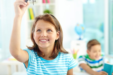 schoolmate: Portrait of smiling girl doing sums on transparent board with schoolmate on background