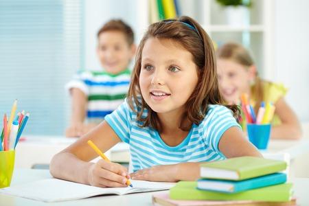 escuela primaria: Retrato de niña linda y sus dos compañeros de escuela en el fondo mirando algo atentamente lección