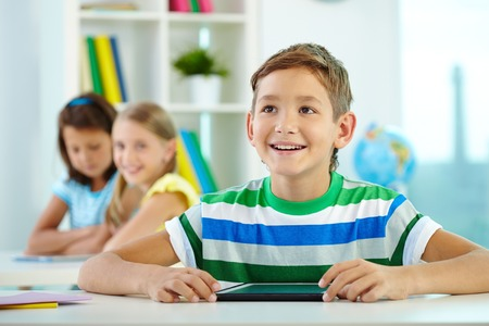Portrait of smart lad at workplace looking at teacher with his classmates on background photo