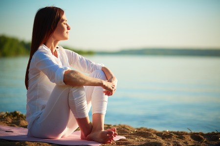 푸른 하늘 야외에서 모래 해변에 앉아 고요한 여자의 측면보기