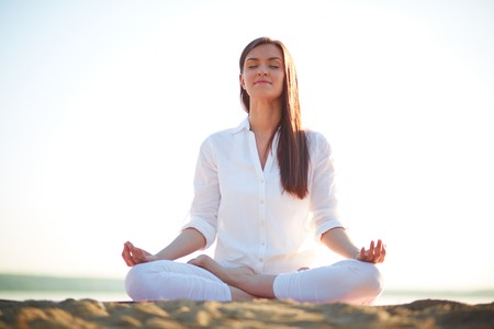 Meditating woman sitting in pose of lotus against clear sky outdoors Stock Photo