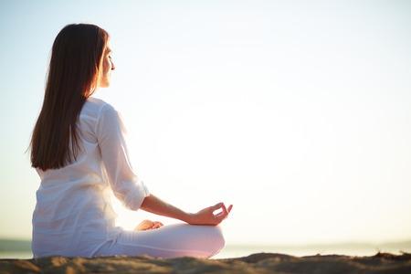 personas sentadas: Vista lateral de la mujer meditando sentado en pose de loto al aire libre contra el cielo claro Foto de archivo