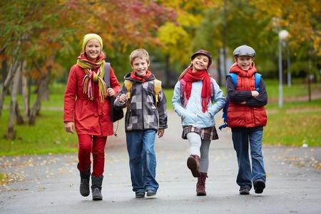 niÑos contentos: Retrato de niños de colegio feliz que va a la escuela Foto de archivo