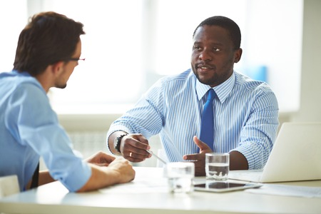 Image of two young businessmen interacting at meeting in office Stockfoto
