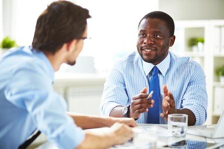 gente comunicandose: Imagen de dos jóvenes empresarios que interactúan en la reunión en la oficina Foto de archivo