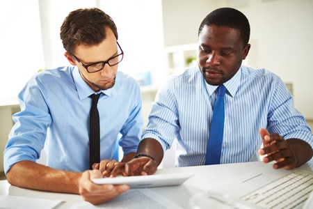 Image of two young businessmen using touchpad at meeting Фото со стока