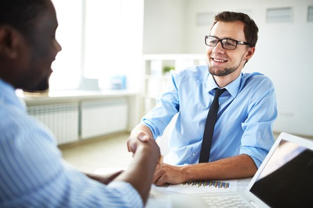 Image of two young businessmen making deal at meeting in office Imagens