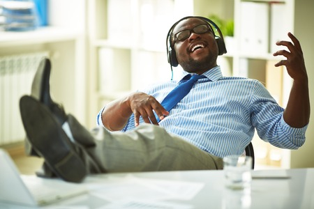 Image of young businessman taking pleasure in listening to his favourite music in office Stock Photo