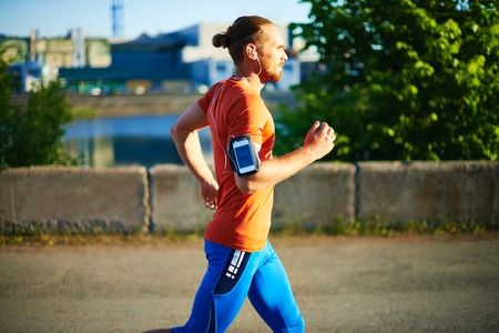 Portrait of young attractive sportsman running outside  Stock Photo