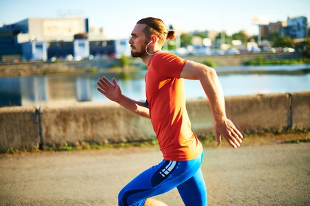 activewear: Portrait of young attractive sportsman with earphones running outside  Stock Photo