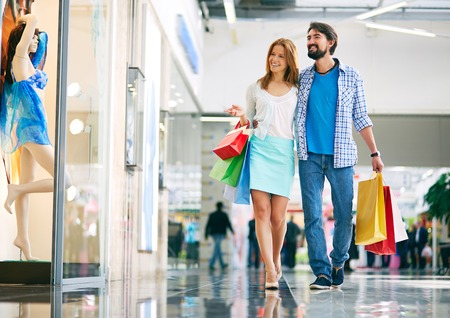 go inside: Portrait of young couple shopping in the mall