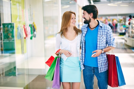 go inside: Portrait of happy young couple interacting while shopping in the mall