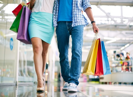go shopping: Legs of young couple going in the mall