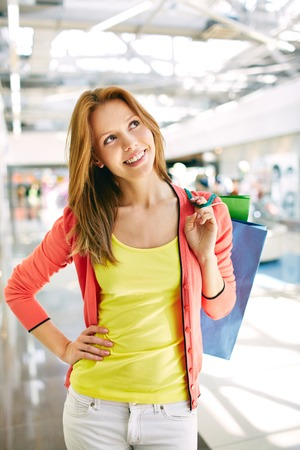 shopaholism: Portrait of happy girl with shopping bags in the mall