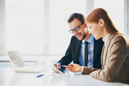 Image of two young business partners using touchpad at meeting Stock Photo