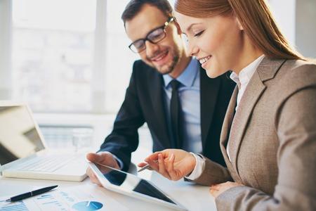 Jonge zakenvrouw uitleggen rapport aan haar collega op de vergadering van Stockfoto