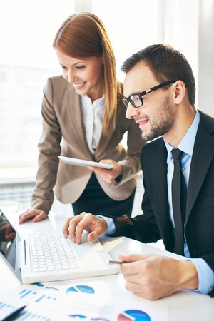 business training: Image of two successful business partners working at meeting in office
