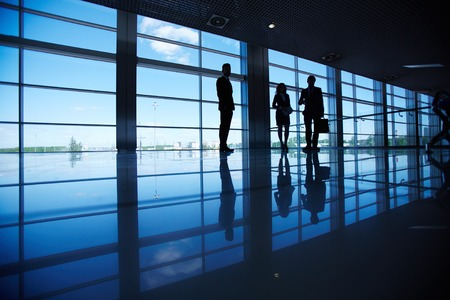 Silhouettes of several office workers standing by the window photo