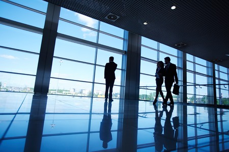go inside: Silhouettes of office worker standing by the window and two business partners communicating while walking near by Stock Photo