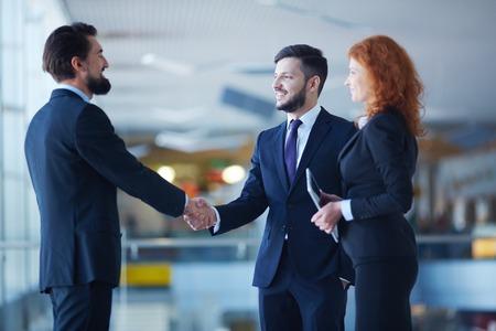 Two businessmen handshaking after striking grand deal
