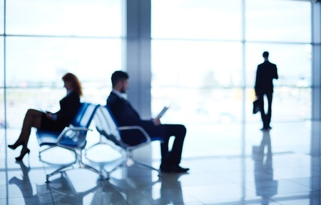 corporate travel: Two business partners reading at the airport while their colleague standing by the window