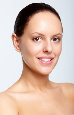 Gorgeous woman looking at camera with smile over white background photo