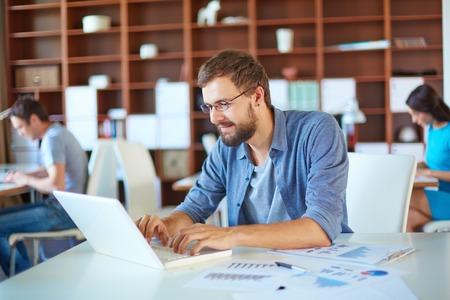working environment: Handsome businessman in casual networking in office in working environment