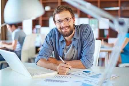 オフィスの彼のパートナーの背景にカジュアルな作業のハンサムなビジネスマン