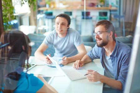 puesto de trabajo: J�venes socios de negocios compartiendo y discutiendo ideas en la reuni�n en la oficina