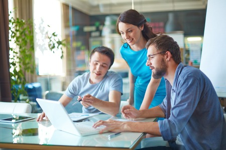tecnologia: Gruppo di tre partner d'affari di successo a dati che parlano di casuale in computer portatile alla riunione in ufficio