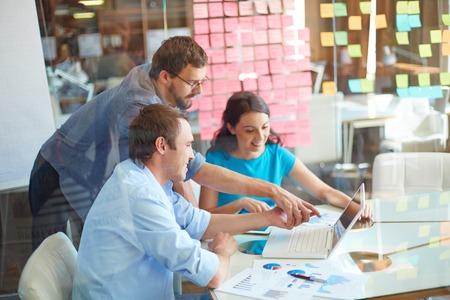 strategy: Grupo de los tres socios de negocios exitosos en casual mirando a la pantalla del ordenador port�til, mientras que dos j�venes que apunta a que en la reuni�n en la oficina