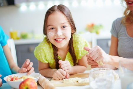 kneading: Portrait of happy girl with floured nose looking at camera with her mother and sister near by Stock Photo