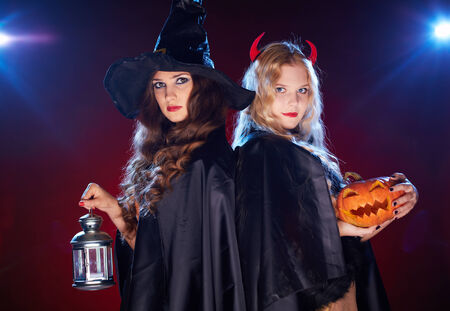 Portrait of two females with lantern and pumpkin looking at camera in the dark photo