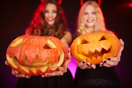 antichrist: Two happy females holding carved Halloween pumpkins
