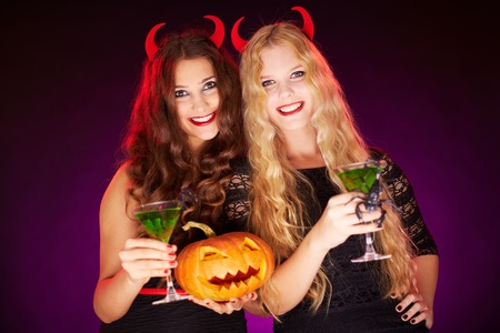 Photo of smiling females holding Halloween pumpkin and cocktails with scorpions photo