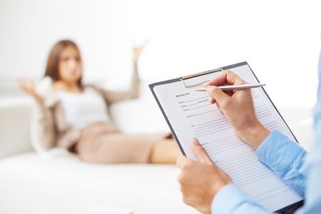 Professionele psychiater raadplegen haar patiënt en het maken van aantekeningen in aanvraagformulier Stockfoto