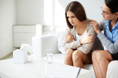 empatia: Imagen del psiquiatra joven que conforta a su triste paciente