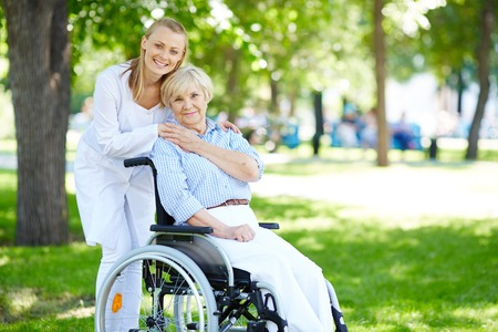 Pretty nurse and senior patient in a wheelchair looking at camera outside photo