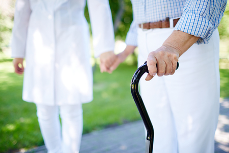 Close-up of disabled female hand holding cane with her doctor walking near by photo
