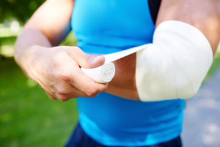 personal injury: Close-up of male bandaging his arm Stock Photo