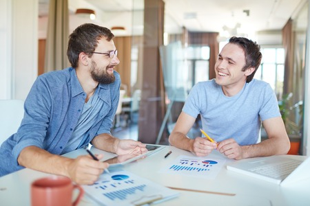 Image of two young businessmen interacting at meeting in office photo