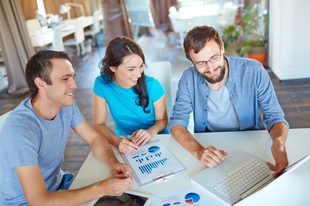 Group of three successful business partners in casual discussing computer project at meeting in office Stock Photo