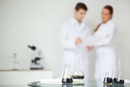 Test-tubes with liquid oil on background of two scientists working in laboratory Foto de archivo