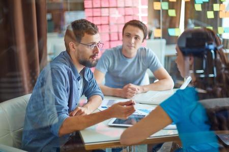 gente comunicandose: Joven consulta su socio de negocios en la reunión en la oficina Foto de archivo