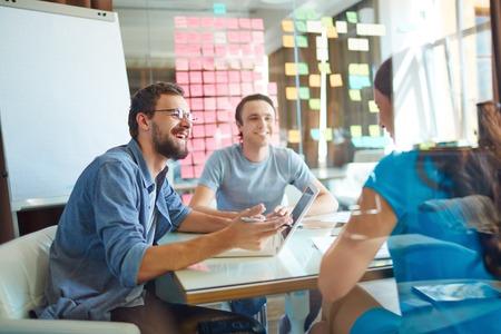 oficina: J�venes socios de negocios compartir y discutir ideas en la reuni�n en la oficina