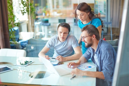 job occupation: Group of three successful business partners in casual using laptop at meeting in office Stock Photo