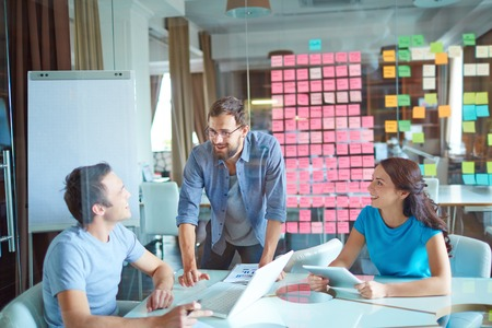Group of three successful business partners in casual communicating at meeting in office Stockfoto
