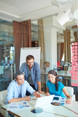 explanations: Group of three successful business partners in casual looking at laptop screen and listening to young man explanations at meeting in office