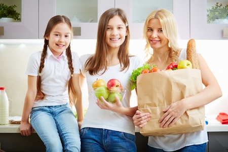 mothers group: Portrait of happy mother and two daughters looking at camera in the kitchen