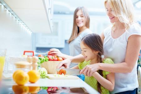 kitchen knife: Retrato de la madre feliz y dos hijas para cocinar en la cocina Foto de archivo
